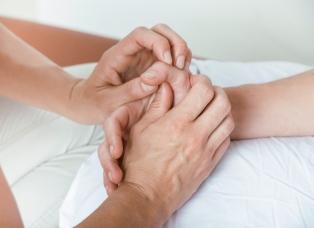 Therapeutin Miriam Wagner führt mit ihren Händen passive Bewegungen am Daumengrundgelenk der Patientin durch