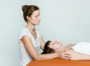 Therpeutin Miriam Wagner sitzt am Kopfende der Patientin und hat beide Hände jeweils auf die Schulter der liegenden Patientin gelegt